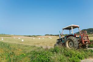 トラクターと刈り取られた牧草地の写真素材 [FYI01709902]