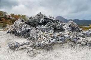 遠くに釜伏山を見る暗雲立ちこめる恐山の岩の写真素材 [FYI01709993]