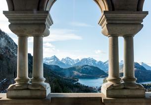 ノイシュヴァンシュタイン城飾り柱越しに山並みと湖を見るの写真素材 [FYI01710036]