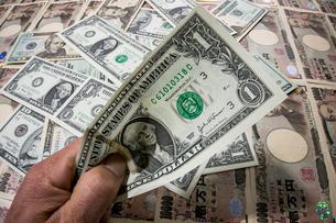 一面のドルと円紙幣をバックに手で掴む1ドル紙幣の写真素材 [FYI01710178]
