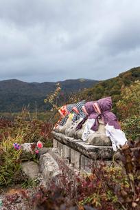 暗雲立ちこめる恐山の頭巾を被ったお地蔵さんが並ぶ風景の写真素材 [FYI01710202]