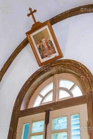 江上天主堂アーチ窓辺にキリストの絵画を見る風景の写真素材 [FYI01710599]