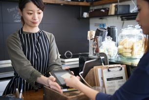 お店で電子決済をしている女性の写真素材 [FYI01710678]