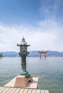 厳島神社唐金燈籠越しに大鳥居と瀬戸内の山並みを見るの写真素材 [FYI01710706]