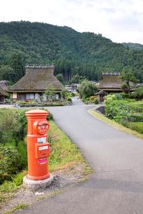 だるまポストと茅葺き屋根民家を見る風景の写真素材 [FYI01710726]