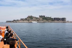 ツアー客越しの軍艦島の写真素材 [FYI01710878]