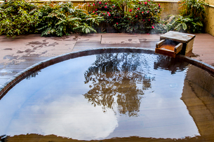 お湯の流れ出る露天風呂の湯船に樹木が映り込む風景の写真素材 [FYI01711026]
