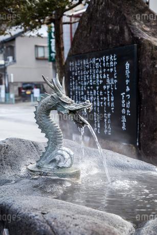 下呂温泉の歴史が書かれた石板を背景に竜の口から温泉水が流れ出る風景の写真素材 [FYI01711027]