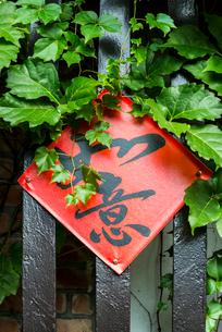 ツタの絡まる柵に貼られた如意の文字の写真素材 [FYI01711151]