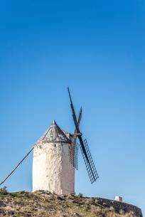 青空のもと丘の上に建つ1基の風車の写真素材 [FYI01711164]