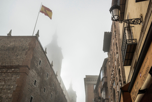 霧で霞むトレド大聖堂の尖塔を背景にスペイン国旗を見るの写真素材 [FYI01711208]