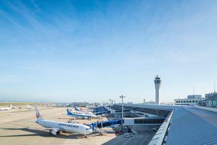 青空のもと管制塔と駐機中の旅客機を見る風景の写真素材 [FYI01711242]