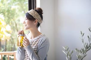 アイスティーを紙ストローで飲んでいる女性の写真素材 [FYI01711296]