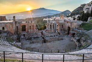日没前の夕日とエトナ山を見るギリシャ劇場の写真素材 [FYI01711600]
