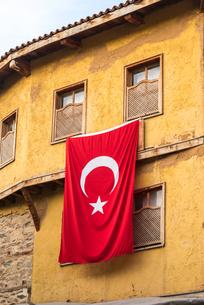 ジュマルクズックの伝統様式家屋に掲げられたトルコ国旗の写真素材 [FYI01711705]