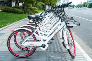 道路沿いの歩道に並ぶレンタル自転車の写真素材 [FYI01711899]