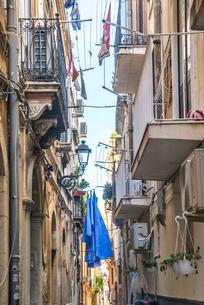 建物が密集する路地に洗濯物を見上げるの写真素材 [FYI01712191]