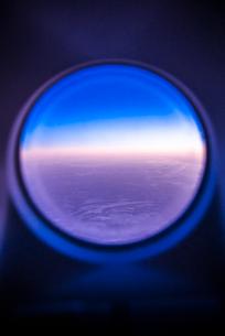 飛行機の丸窓からマジックアワーの風景を見るの写真素材 [FYI01712275]