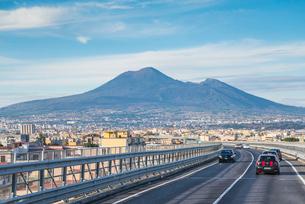 自動車道から見るヴェスヴィオ火山と裾野に広がる街並みの写真素材 [FYI01712320]