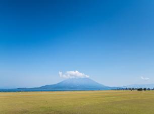 芝生広場越しに見る雲かかる桜島の写真素材 [FYI01712396]