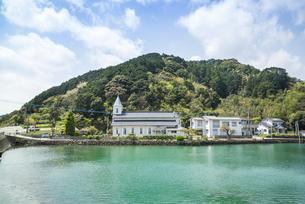小高い山を背景に建つ水辺の中の浦教会の写真素材 [FYI01712482]