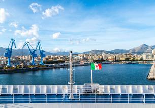 フェリーデッキに靡くイタリア共和国商船旗越しにパレルモ港を望むの写真素材 [FYI01712583]