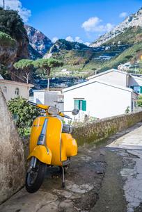 道端に駐車中の黄色のスクーターを見るアマルフィ風景の写真素材 [FYI01712595]