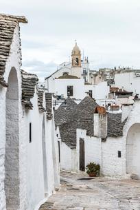 教会の鐘楼を見るアルベロベッロのトゥルッリ風景の写真素材 [FYI01712610]