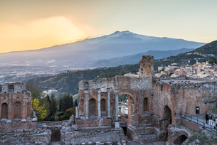 ギリシャ劇場越しに夕焼けのエトナ山とタオルミーナの街並みを見るの写真素材 [FYI01712783]