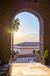ギリシャ劇場入り口アーチ越しに遠く霞みがかったエトナ山を望むの写真素材 [FYI01715067]