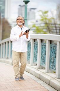 橋の上でタブレットPCを操作するシニア男性の写真素材 [FYI01717015]