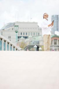 橋の上でタブレットPCを操作するシニア男性の写真素材 [FYI01717040]