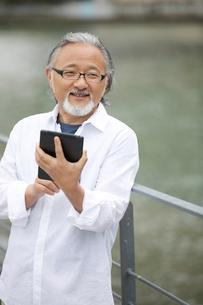 タブレットPCを操作するシニア男性の写真素材 [FYI01717187]