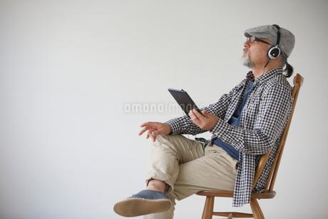 ヘッドホンを聴きながらタブレットPCを持つシニア男性の写真素材 [FYI01717306]