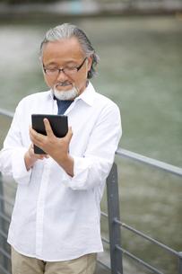 タブレットPCを操作するシニア男性の写真素材 [FYI01717387]