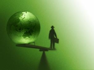シーソーに乗るスーツ姿の男性と地球(黄緑色)の写真素材 [FYI01717555]
