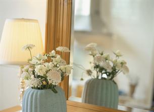 鏡台の前の花瓶に生けられた花の写真素材 [FYI01717644]