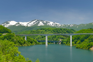 新緑の月山湖と山形自動車道と月山の写真素材 [FYI01719764]
