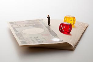 札束とビジネスマンとさいころの写真素材 [FYI01720732]