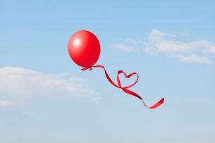 赤い風船とハートのリボンの写真素材 [FYI01724622]