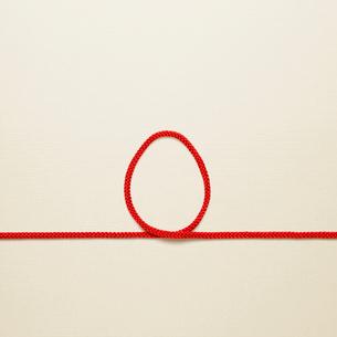 赤い紐でつくったニワトリ(酉)の卵のイメージの写真素材 [FYI01725563]