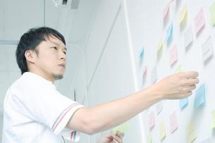 壁に付箋を貼る男性の写真素材 [FYI01725833]