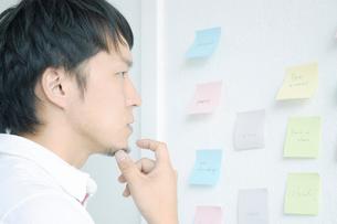 付箋の貼られた壁の前で考える男性の写真素材 [FYI01725985]
