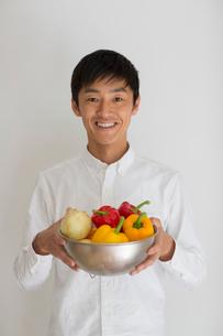室内で野菜の入ったカゴを持つ笑顔の男性の写真素材 [FYI01726156]