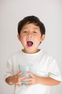 室内でコップの牛乳を飲み干した子供の写真素材 [FYI01726212]