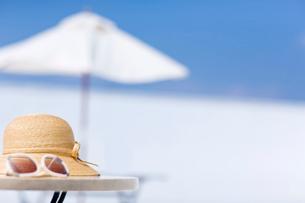 テーブルに置かれたサングラスと麦わら帽子の写真素材 [FYI01726285]