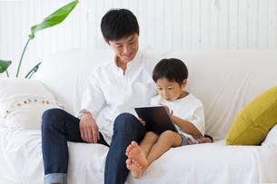 リビングのソファでタブレット端末を使う子供とパパの写真素材 [FYI01726292]