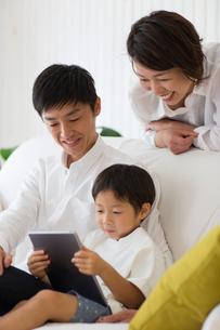 リビングのソファでタブレット端末を使う子供とパパとママの写真素材 [FYI01726303]