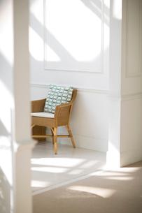 陽射しの入る白い部屋にある藤の椅子の写真素材 [FYI01726311]
