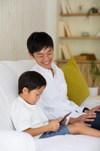 リビングのソファでタブレット端末を使う子供とパパの写真素材 [FYI01726352]